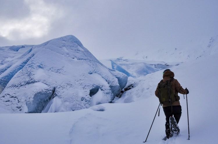 person snowshoeing near glacier in Alaska