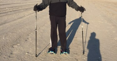 man posing with snowshoes and poles on sand