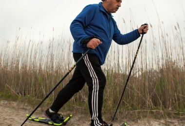 man using snowshoes and poles on sand