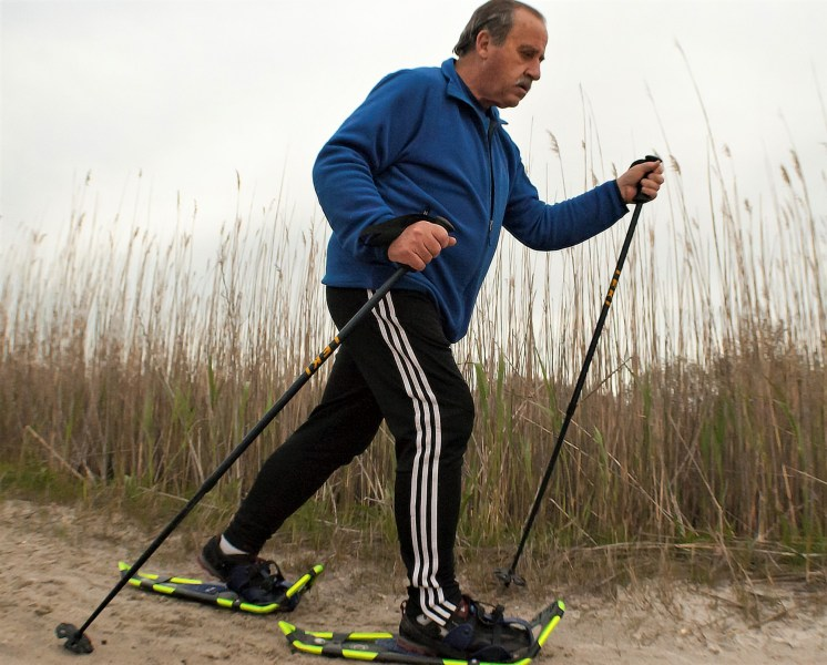 sandshoeing for WWF 5K: man using snowshoes and poles on sand