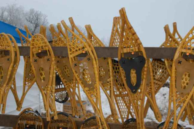 many wooden snowshoes laying against a fence