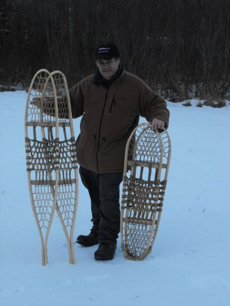 traditional snowshoes: man holding two pairs of traditional snowshoes