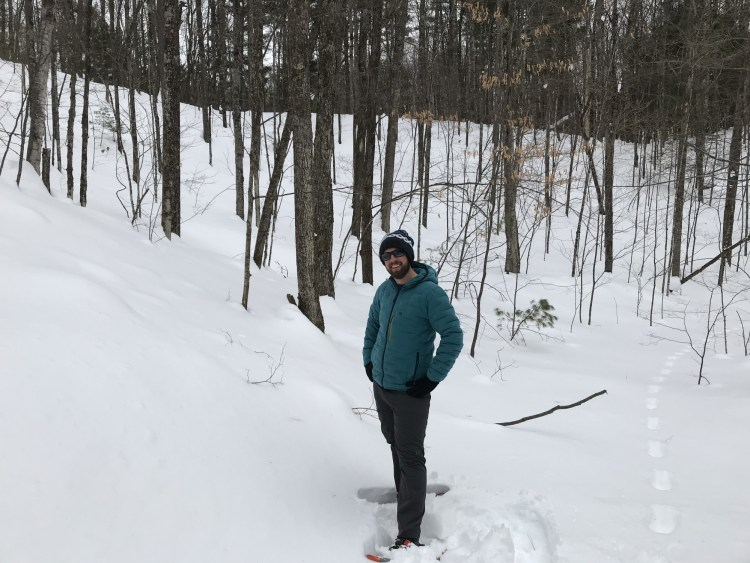man on snowshoes with trees in background smiling in deep snow