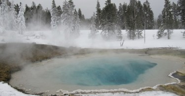 geyser in Yellowstone National Park surrounded by snow