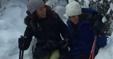 two females laughing while snowshoeing