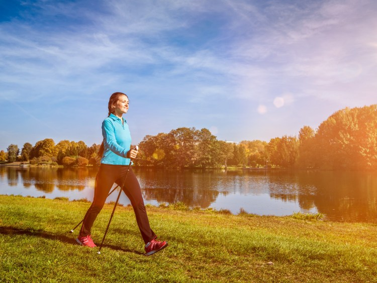 woman walking in park with nordic walking poles