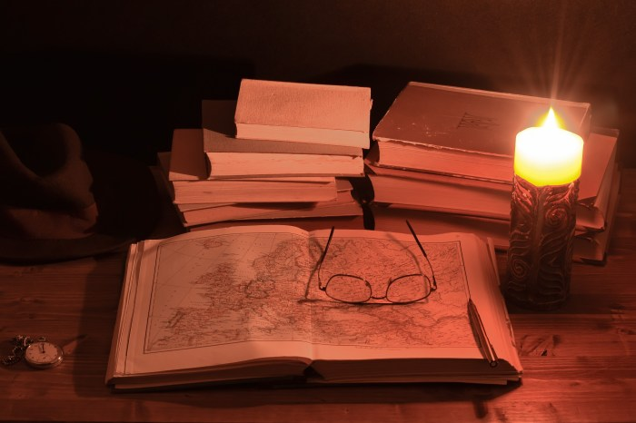 treasure map next to a candle and other books