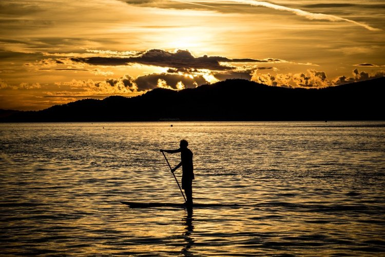 paddle boarder on water during sunset with mountains in background