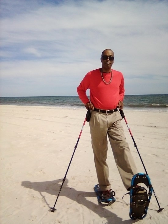 snowshoes on sand for fitness: man wearing snowshoes on sand lifting up snowshoe
