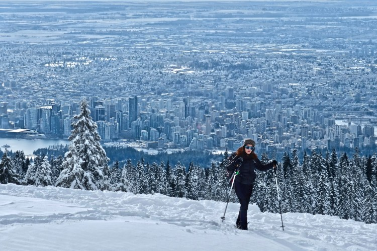 snowshoer on Cypress Mountain with view of Vancouver in background