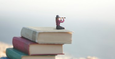 miniature woman on top of books with spyglass
