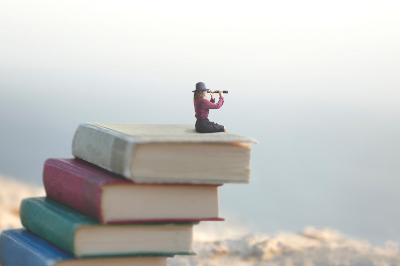 miniature woman on top of outdoor adventure books with spyglass