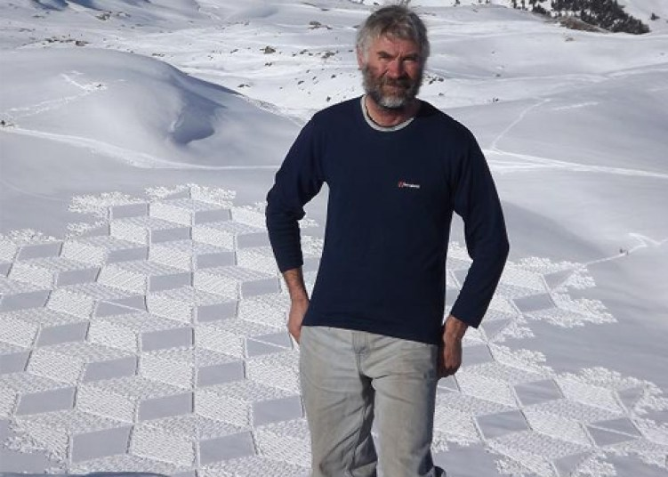 snow artist Simon Beck standing in front of one of his designs