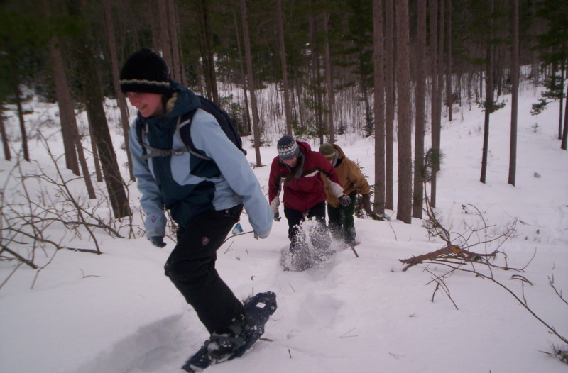 snowshoeing health benefits: students going up hill in snowshoes