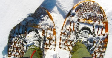looking down at traditional wooden snowshoes with boots