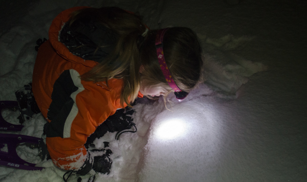 girl with headlamp snowshoeing at night
