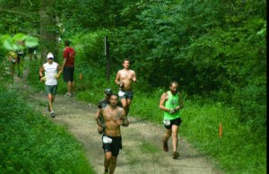 Chukuske Running into Daylight at the Afton 50km, Afton, Minn, flashing his tattoos. The ink represents he told me different periods of his life including personality and interests. Sometime ask him to explain their meaning; at least three are running related.