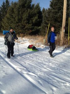 Co-RD Chris Scotch (R) and Nathan Jackson demonstrate 2 ways to carry the required load. The sled is most popular (photo courtesy FB Helen Lavin)