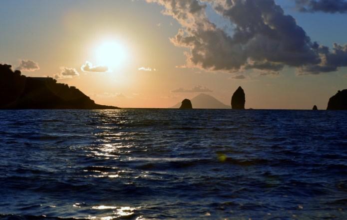 """I Faraglioni tra l'isola di Vulcano e quella di Lipari al tramonto, in controluce. Sullo sfondo la """"piramide"""" dell'Isola di Stromboli"""