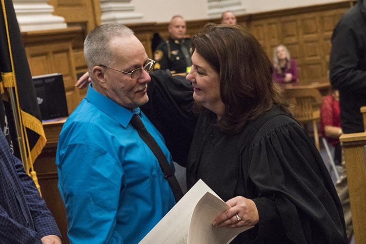 Stark County Common Pleas Judge Taryn Heath gives a certificate and hug to graduate Timothy Spickler.