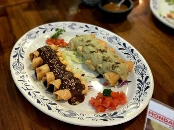 Pollo and papas taquitos topped with mole.
