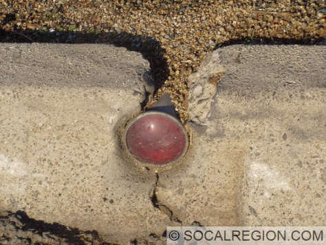 Old reflector in the 1930's curbing at the Pomona Blvd junction.