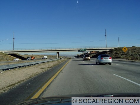 Northbound at Ave N, the freeway is recessed for a while, creating a more urban feel in the middle of the desert.