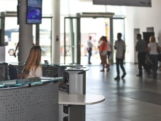 Woman sitting at a reception desk, looking away towards an open door with people milling around it