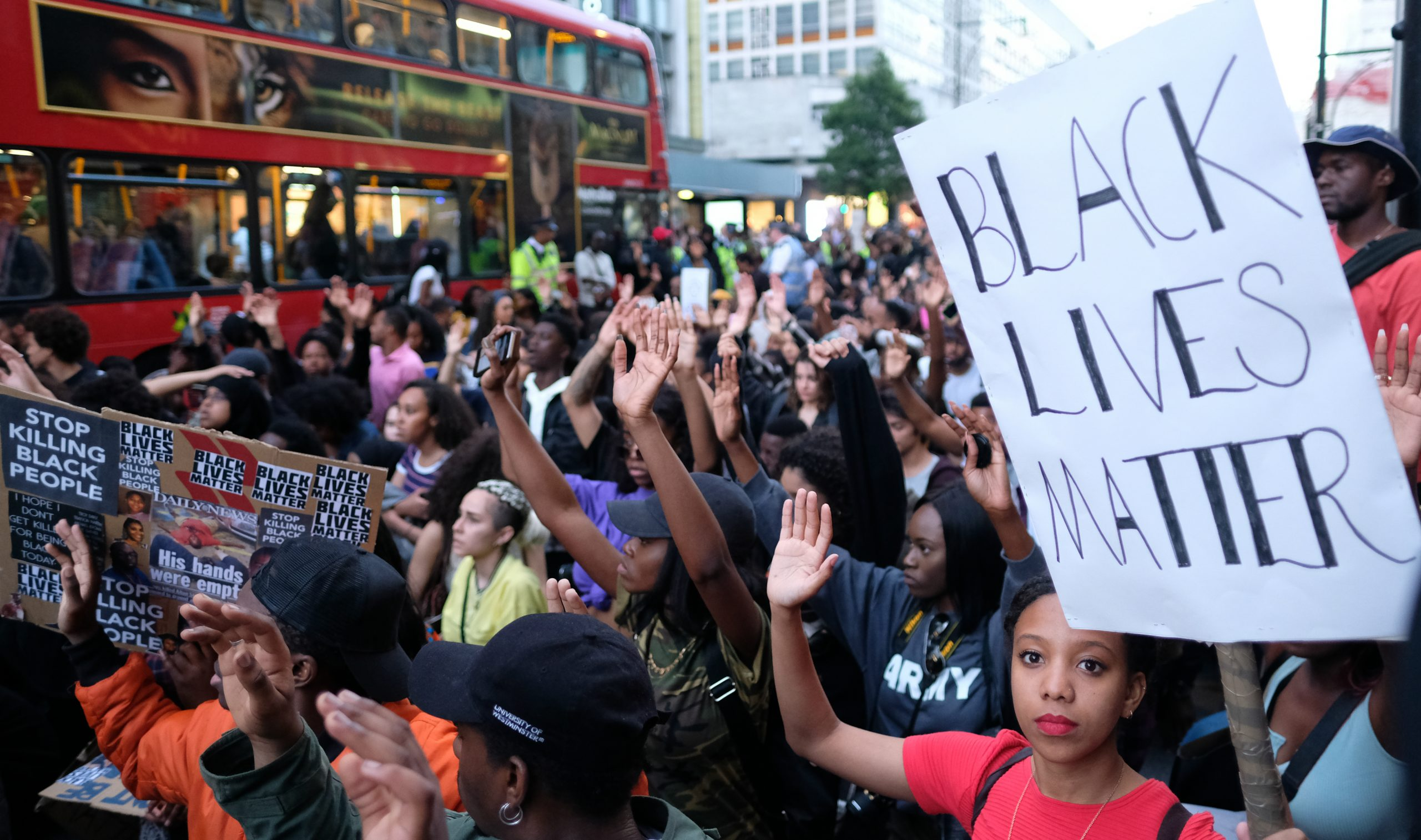Black Lives Matter protesters in London's Oxford Street kneel and raise their hands – 8 July 2016