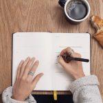 Schrijvende handen van enigszins alternatieve vrouw met kop koffie en croissant met een hap er uit