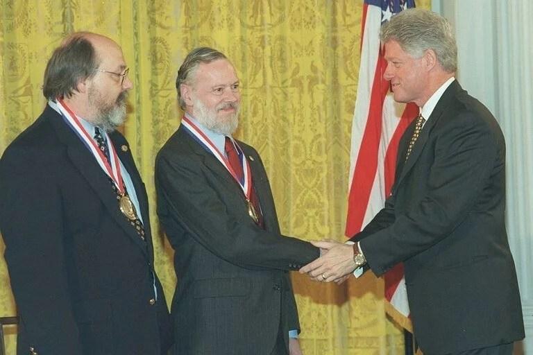 Ken Thompson y Dennis Ritchie reciben el saludo de Bill Clinton en la entrega de la Medalla Nacional de Tecnología de los Estados Unidos; ambos crearon el sistema operativo Unix, cuya descendencia llega hasta hoy