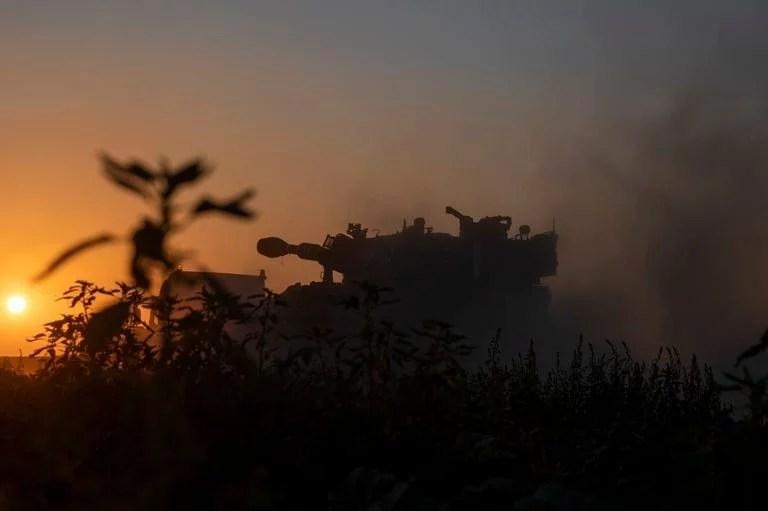 Un camión lleva una unidad de artillería a una posición en la frontera israelí en Gaza