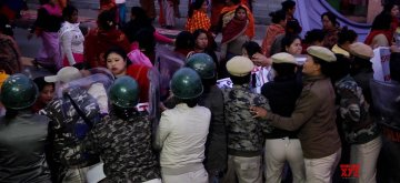 Imphal: Police prevent women vendors from continuing their sit-in protest against Citizenship (Amendment) Bill that they started on Saturday in the main market complex in Imphal, on Feb 10, 2019. (Photo: IANS)