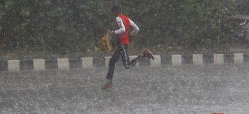 Gurugram: A boy runs for shade as heavy rains lash Gurugram, on May 17, 2019. (Photo: IANS)