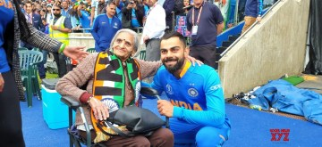"Birmingham: India skipper Virat Kohli greets 87-year-old Charulata Patel, who became a social media sensation after an image of her blowing a horn to cheer the Men in Blue during their World Cup match against Bangladesh went viral, at the Edgbaston Cricket Ground on July 2, 2019. ""I have been watching cricket for last many decades. Earlier, I used to watch on TV when I was working, but now that I am retired I watch it live,"" she said. (Photo: IANS)"