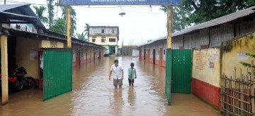 Kamrup: A school partially sub-merged in water in the flood-affected Chhaygaon of Assam's Kamrup district. (Photo: IANS)