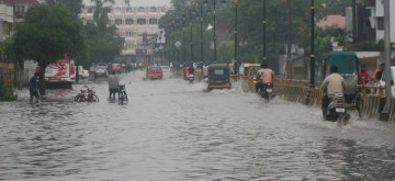 Varanasi: Vehicles wade through a water-logged street after heavy rains, in Varanasi on July 11, 2019. (Photo: IANS)