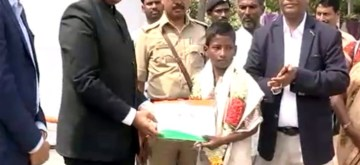 Twelve-year-old brave heart Venkatesh being felicitated by Raichur district Deputy Commissioner B. Sharat at Raichur in Karnataka's northern region on the 73rd Independence Day on Thursday for risking his life in escorting an ambulance across a submerged bridge recently.