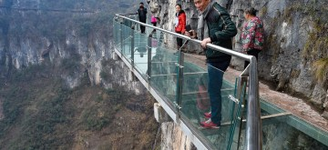 (160224) -- TONGREN, Feb. 24, 2016 (Xinhua) -- Tourists walk on a glass skywalk in the National Mine Park of Tongren City, southwest China's Guizhou Province, Feb. 24, 2016. The 1,005-meter-long and 1.6-meter wide glass skywalk, with more than 100 meters above the valley bottom, has passed a safety test and will be opened to the public in May.  (Xinhua/Liu Xu) (dhf)
