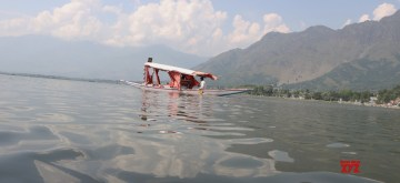 Srinagar: A boatman ferries a tourist on a Shikara across the waters of Dal Lake, in Srinagar on July 16, 2019. (Photo: IANS)