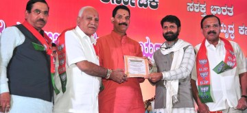 Bengaluru: BJP State President Nalin Kumar Kateel receives letter from Karnataka Chief Minister BS Yeddiyurappa during a charge taking ceremony of Nalin Kumar Kateel as a BJP State President at Palace Grounds in Bengaluru on Jan 16, 2020. Also seen Union Ministers DV Sadananda Gowda, Prahalad Joshi, DCMs Govind Karjola, Dr. Ashwath Narayan and Minister CT Ravi. (Photo: IANS)