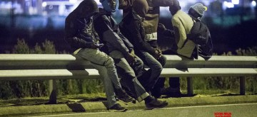 CALAIS, Aug. 9, 2015 (Xinhua) -- Migrants linger on the Shuttle railroad looking for a chance to jump over the fence and access the Channel Tunnel, in Calais, northern France, Aug. 6, 2015. Calais, where the French end of the Channel Tunnel is located, has been flooded by growing flows of migrants mainly from Libya, Eritrea, Sudan and Syria who fled war, insecurity and poverty. Camping out in Calais zone, they are trying to board lorries and trains heading to Britain in hope to find a better life in London. (Xinhua/Franck Mahe/IANS)