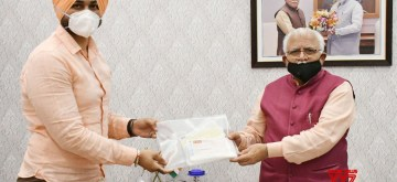 Chandigarh: Haryana Chief Minister Manohar Lal Khatar being presented with 150 cheques amounting to Rs 34,41,111 by the Minister of State for Sports and Youth Affairs, Sandeep Singh, contributed by the people of his constituency, Pehowa, for the Corona Relief Fund in Chandigarh on Apr 9, 2020. (Photo: IANS)