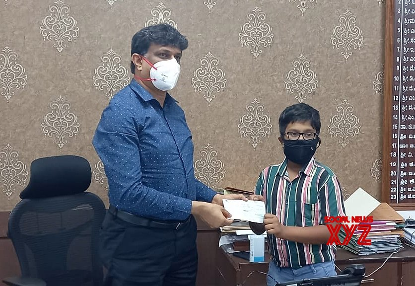 Bengaluru : 12 year old Mayank who is studying in 7th standard presenting rupees 4,190 saved from past 4 years to DC J Manjunath for CM COVID - 19 relief fund, in Bengaluru. #Gallery
