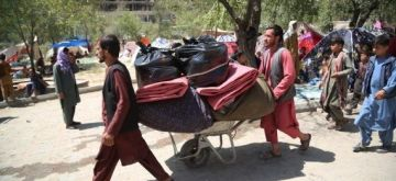 Afghan displaced people who fled from their homes during the fights carry their belongings in a public park in Kabul, Afghanistan, Aug. 11, 2021. (Photo by Sayed Mominzadah/Xinhua/IANS)