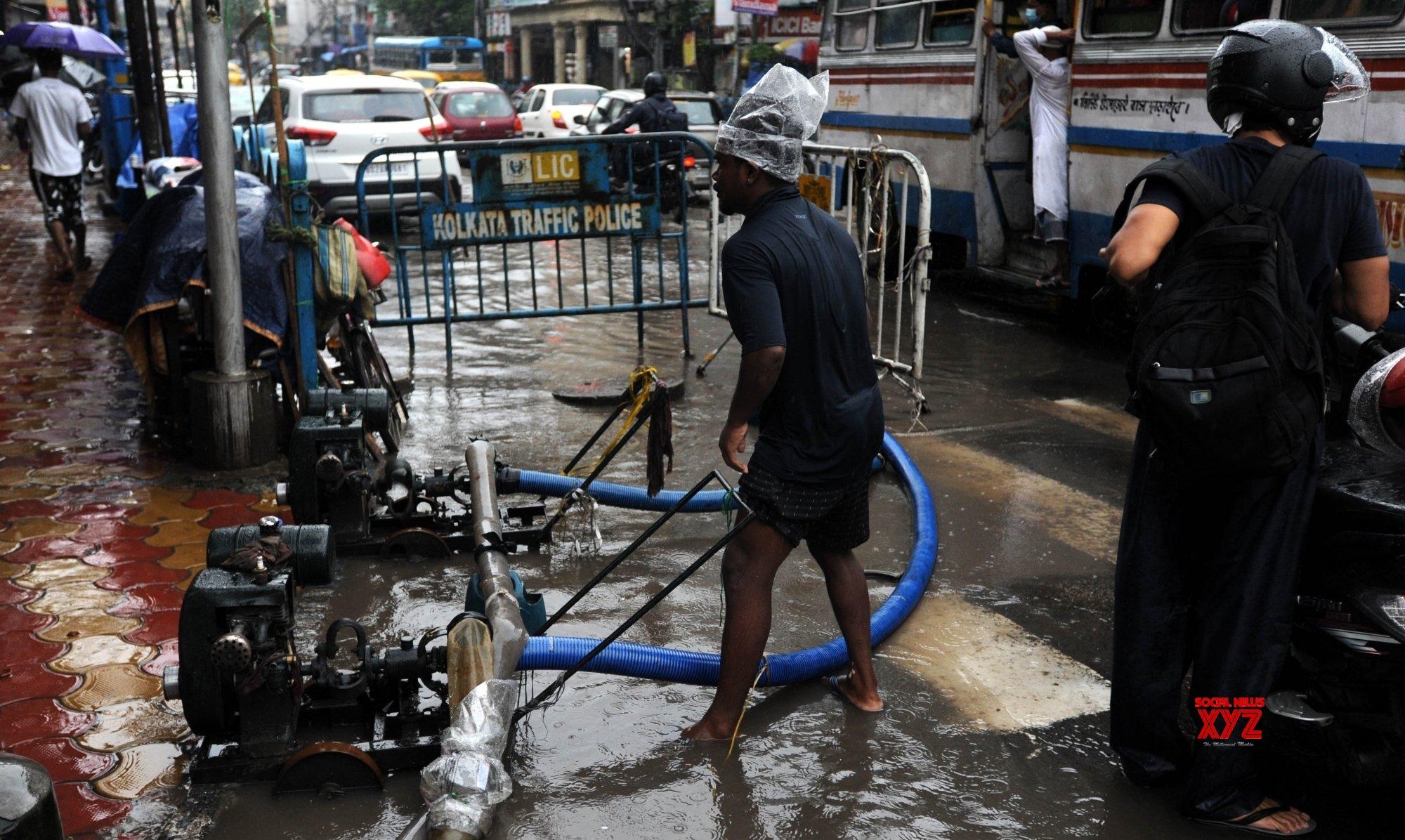 Kolkata: Commuters wade through waterlogged street after heavy rains lash city in Kolkata. #Gallery