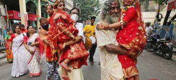 Kolkata: Hindu priests guide a young unmarried girls known as 'Kumari', who dress up as the Hindu goddess Durga on Maha Ashtami Puja, during a ritual for the Durga Puja festival at a community puja pandal in Kolkata on Wednesday, October 13, 2021.(Photo: Kuntal Chakrabarty/IANS)