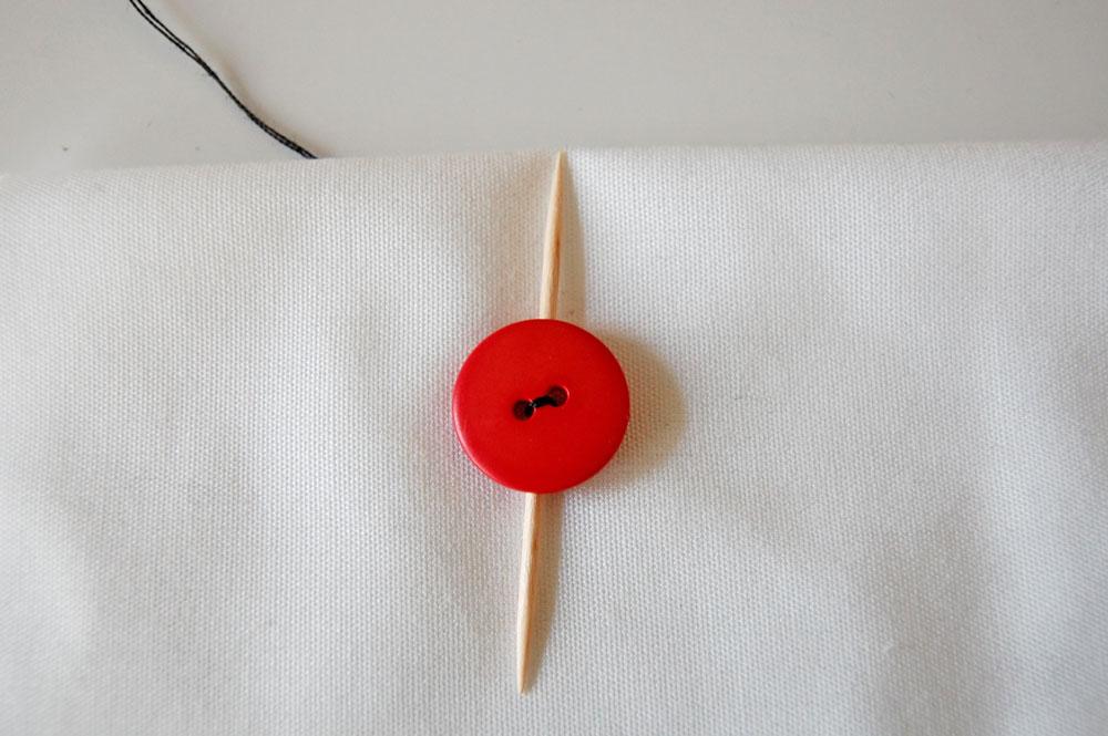 Knopf annähen - Zahnstocher zwischen Knopf und Stoff knopf annähen Zugeknöpft - Knopf annähen - So einfach geht es.