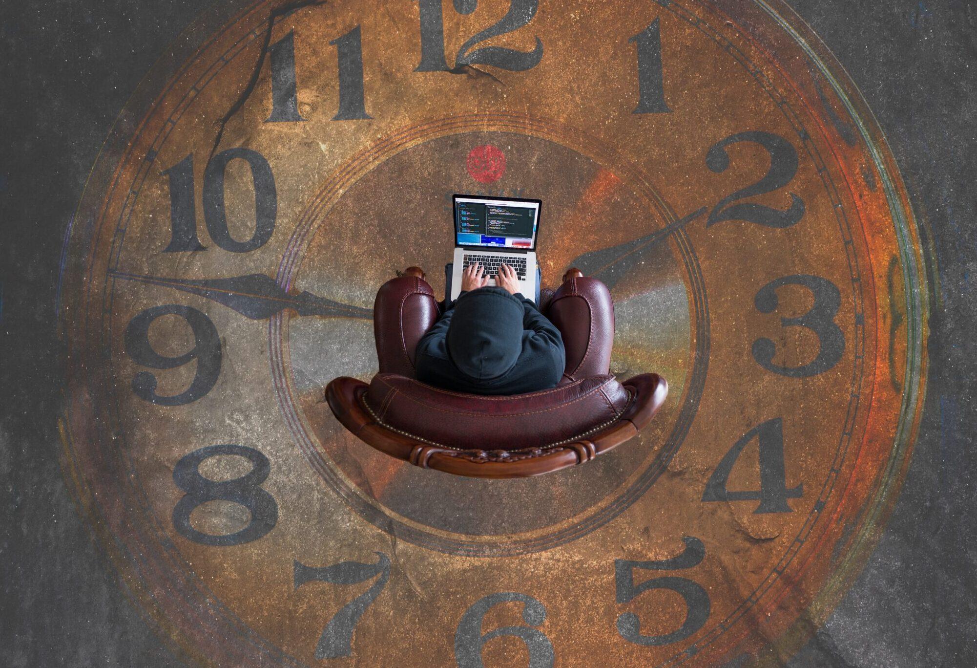 Uhr mit Person in der Mitte mit Laptop