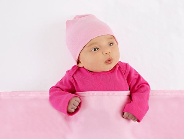 Baby wearing pink with a pink blanket